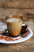 stock photo of bittersweet  - Glass of milk with chocolate chunks and cocoa on rustic wooden planks background - JPG