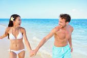 picture of laugh  - Beach couple having fun happy on beach vacation during summer holiday - JPG