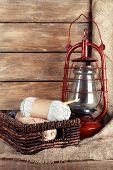 picture of kerosene lamp  - Kerosene lamp with yarn and needles for knitting in wicker basket on wooden planks background - JPG