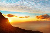 picture of mountain sunset  - Sunset above the sea with sun blue sky clouds and mountain - JPG