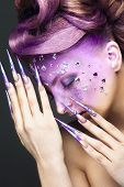 image of long nails  - Girl with bright purple creative makeup with crystals and long nails - JPG