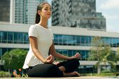 picture of knee  - Young stressed hispanic business woman doing yoga outside office building sitting in lotus position with hands on knees in the street. Concept of long working hours and need of stress free break