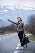 stock photo of independent woman  - Young woman hitchhiking on countryside road - JPG
