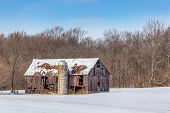 stock photo of silo  - An old and dilapidated barn and silo stand in a snowy landscape on a clear and sunny day - JPG