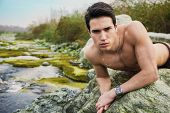 stock photo of shirtless  - Handsome fit shirtless young man laying on rock next to water pond or river looking at camera - JPG