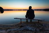 stock photo of bench  - Bench on lake shore at sunset - JPG