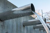 stock photo of flow  - Water flowing out from steel pipes - JPG