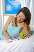 pic of nightgown  - young attractive and beautiful woman in nightgown lying on bed at bedroom holding apple writing diary with pen in relax looking tranquil and happy in American lifestyle concept - JPG