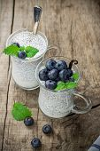 picture of vanilla  - Chia seed pudding made with blueberries vanilla and mint on a wooden background - JPG