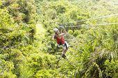 stock photo of jungle  - Woman going on a jungle zipline adventure - JPG