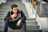 pic of staircases  - Trendy handsome young man in winter fashion sitting on a long staircase leading to an urban commercial building looking to a side with a serious expression - JPG