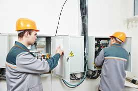 picture of electrical engineering  - two electrician builder engineer works with electric cable wiring of fuse switch box - JPG