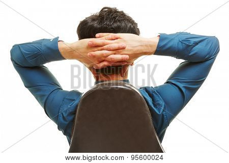 Business man sitting on an office chair from behind with hands behind his head