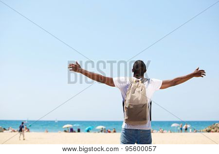 Man Standing With Arms Spread Open At Beach