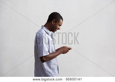Smiling Black Guy Walking And Using Mobile Phone