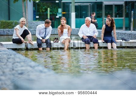 Happy business people talking during break in summer with their feet in water