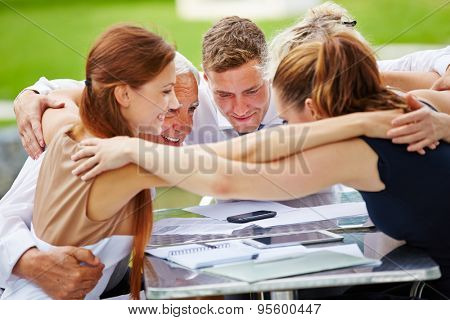 Business people hugging for team spirit in a meeting at a table