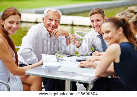Senior CEO doing planning with business team outdoors at a table