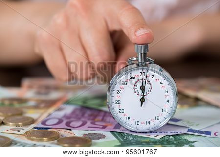 Person Hands With Stopwatch And Coins Over Banknote