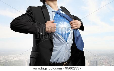 Businessman opening his shirt on chest acting like super hero