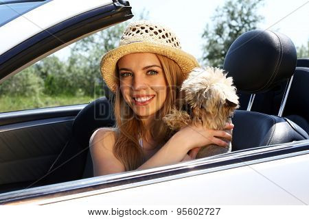 Happy girl with cut dog in cabriolet, outdoors