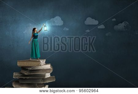 Young woman in green dress with lantern walking in darkness