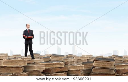 Young businesman standing on pile of old books