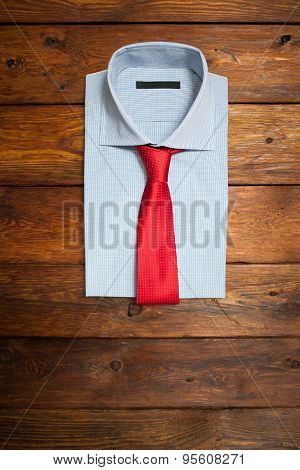 Shirt With Red Tie On A Wooden Brown Background