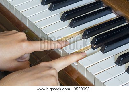 Girl's Hands Two Fingers Holding Pressed  Keys On A Piano