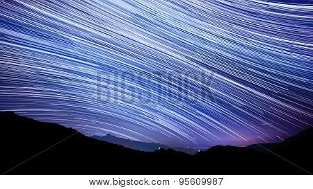 Star Trail Effect Over Mountain Night Sky.
