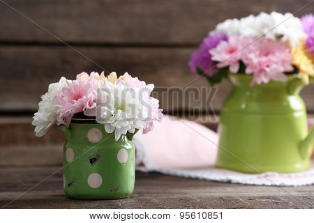 Beautiful chrysanthemums in pitchers on wooden background