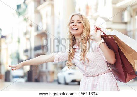 Blond girl having fun after shopping