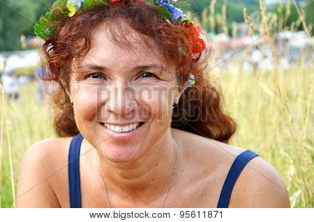 Happy beautiful redhead woman with flowers in her hair in her fourties smilling outdoors