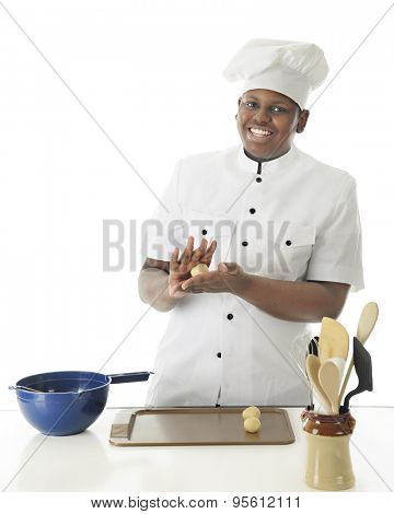 A young chef smiling at the viewer as he hand rolls dough into balls before placing them on the cookie sheet.  On a white background with space on left for your text.