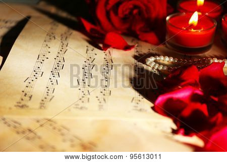 Beautiful roses with candlelight  on music sheets, closeup