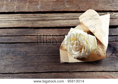 Beautiful rose wrapped on music sheet on wooden background