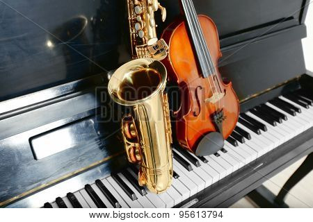 Violin and saxophone on piano background