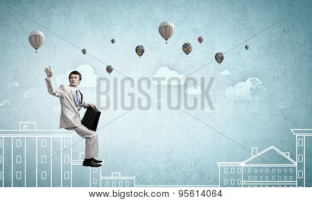 Businessman in white suit with briefcase sitting on building top