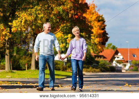 senior couple, Man and woman, having a walk in autumn or fall outdoors, the trees show colorful foliage