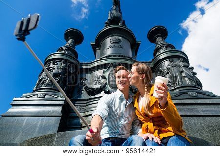 Tourist couple taking selfie on Theaterplatz in Dresden with phone on stick