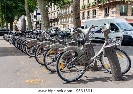 Streetview With Woman Paying For Renting A Bycicle In Paris