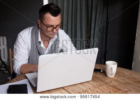 Stylish Man using laptop in startup office