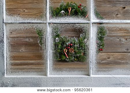 Snow Covered Window With Decorative Christmas Wreath On Rustic Wooden Boards In Background