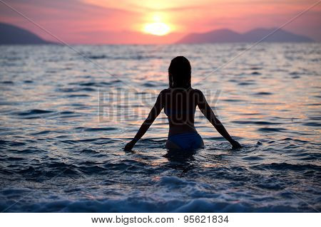 Gorgeous sexy fit woman silhouette swimming in sunset.Free happy woman enjoying sunset.