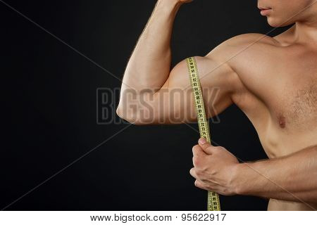 Healthy young sportsman is checking measure of his muscles