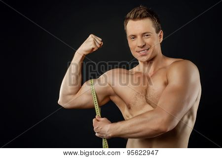 Handsome young bodybuilder is measuring his muscles