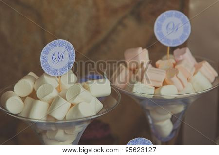 Two glasses of marshmallow sticks at the sweet bar on wedding