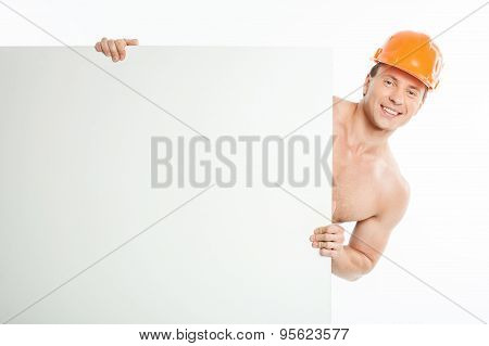 Handsome young builder is peeping through whiteboard