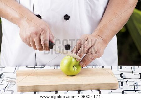Chef's Hands Cutting Green Apple