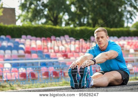 Attractive young athlete is preparing his body before running